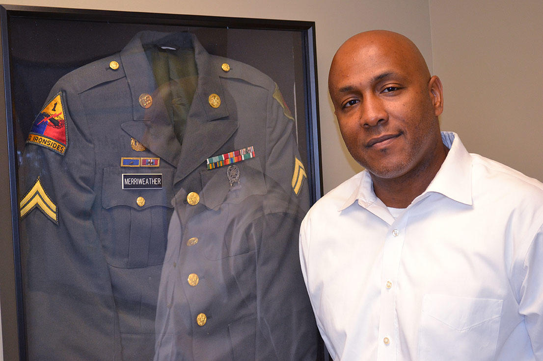 John Merriweather, founder of GO Company USA, Inc. and Desert Storm Veteran, stands proudly beside his Army uniform.